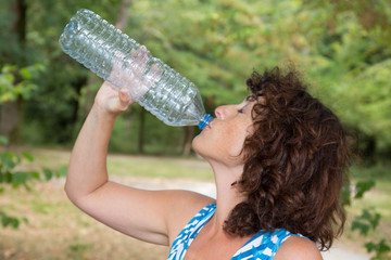 Dark-haired woman wearing blue t-shirt drinking water at green park.