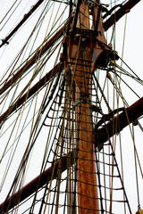 The wooden mast and lots of ropes on a large sailboat. Gray sky above.