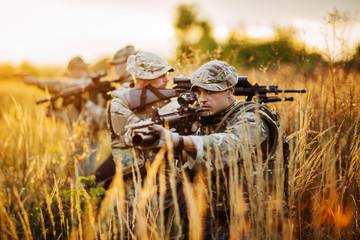 Rangers shooting with his weapon, rifle at sunset. War, army
