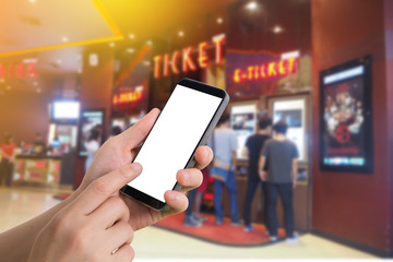 human hand hold and touch smartphone, tablet, cell phone with blank screen on blurry theater,