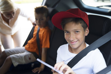 Boys at the back seat with tablet