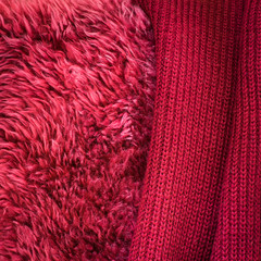 Dark red knitted blanket and red dyed sheepskin. Cosy and warm textiles for autumn decor.