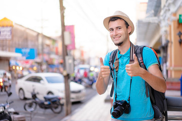 Happy traveling. Young smiling man with backpack and camera showing thumbs up on asian street.