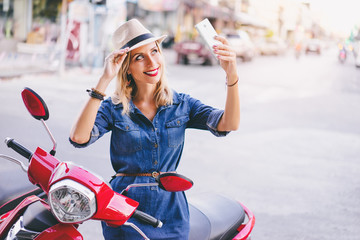 Urban fashion and technology. Pretty young woman in hat using smartphone while sitting on motorbike.