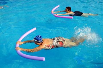 Two senior women doing swimming exercise in pool.