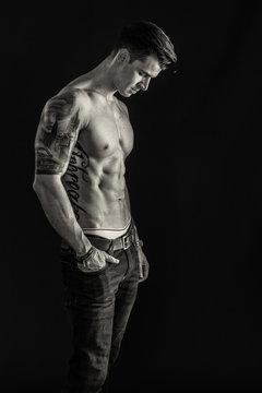 Tätowierter Mann im Seitenprofil in schwarz weiß - Junger Mann mit Tattoos und Sixpack