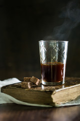 A glass with black coffee on vintage background