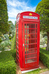 Red London phone booth in a garden