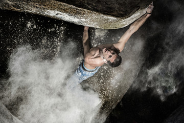 Shirtless young man climbing on mountain