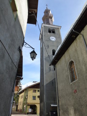 Church spire and traditional stone buildings in historic centre of Bozel, French Alps