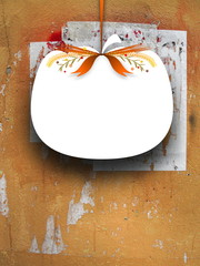 Close-up of one blank pumpkin shaped frame hanged by brown ribbon on cracked and scratched concrete wall background