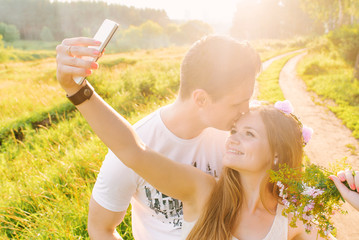 A blonde is making a selfie with her man kissing her forehead smiling happily, sunshine and green fields on the background