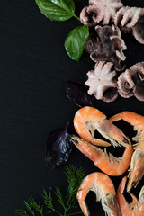 Preparing fresh seafood in the kitchen with gourmet pink shrimp and octopuses surrounded by fresh herbs and spices on black stone background