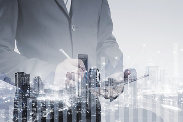 Double exposure of success businessman using digital tablet with city landscape background,business background