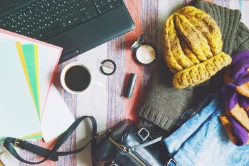 Flat lay fashion background/Stylish women's clothing, handbag, cosmetics and laptop. Light blue jeans, brown wool sweater, yellow hat and striped scarf. Autumn or winter outfit fashion blogger