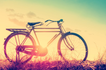 beautiful landscape image with Bicycle at sunset in vintage tone