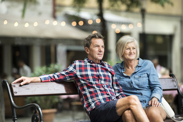 Senior couple sitting on bench watching something