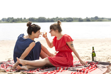 Two smiling friends sitting on the beach toasting with glasses of sparkling wine