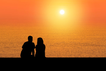 silhoutte rear view romantic couple sit relax watching sunset on the beach