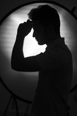 Silhouette of young guy posing in studio