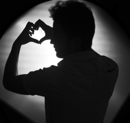 Silhouette of young guy posing in studio drrawing heart by his hand