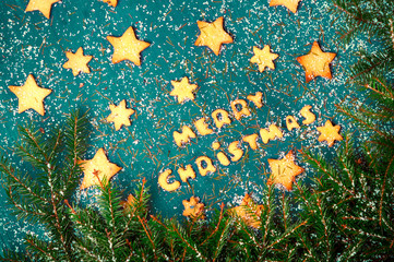 Baking Merry Christmas inscription.Gingerbread cookies.Spruce branches and snow on a blue wooden background.Toned.