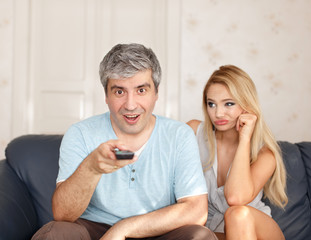 Man switching TV channel with boring wife and marriage