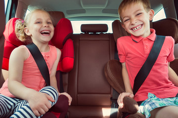 Happy kids, adorable girl with her brother sitting together in m
