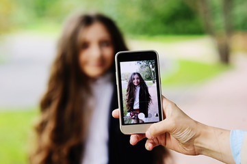 Woman taking a photo of girl with smartphone