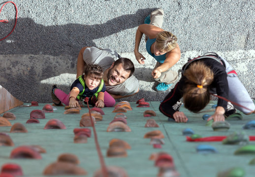 Little baby girl doing first steps on climbing wall