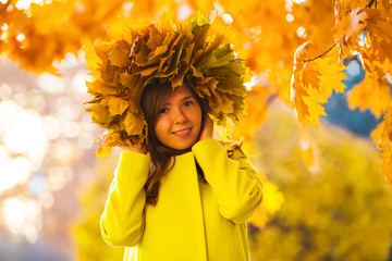 smiling girl in a wreath of yellow autumn leaves