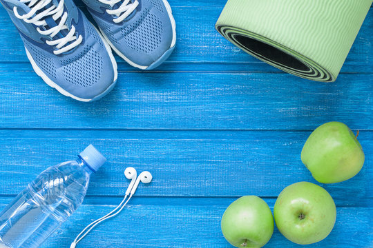 Flat lay sport shoes, bottle of water, mat and earphones on blue