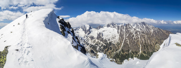 Mountain panorama. Two climbers going thru snow towards the summit. Footpath. Sky is clear. Good weather. High Tatras Slovakia