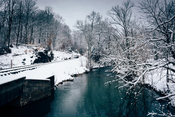 A snow covered railroad track and creek in rural Carroll County,