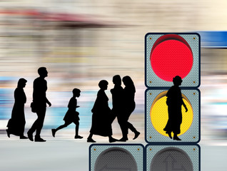 image of silhouettes of people and traffic light close-up