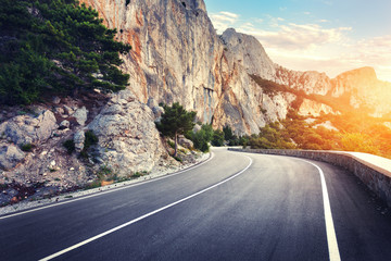 Beautiful asphalt road. Colorful landscape with high rocks, mountain road with a perfect asphalt, trees, blue sky at sunset in summer. Travel background. Highway at mountains with vintage style Wall mural
