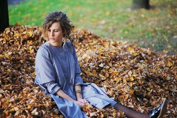 Nice girl sitting on a pile of fallen leaves in autumn park.