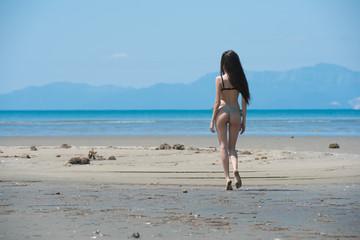 Slim girl wear bikini and walking on a long land of sand, horizontal and full body length photo