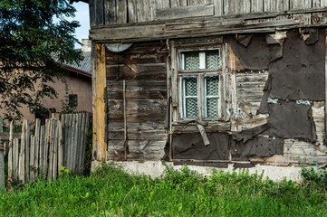 Old wooden, damaged house with window
