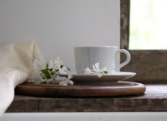 rustic still life. cup of tea on the window sill and white phlox flowers. vintage wooden background. close-up