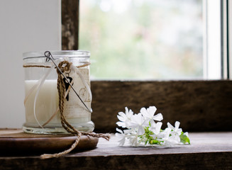 rustic still life. milk in a glass jar, flowers. vintage, wooden background, window and fresh produce