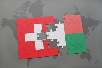 puzzle with the national flag of switzerland and madagascar on a world map background.