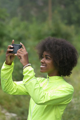Beautiful afro american woman taking photos outdoors in a forest