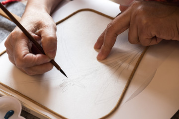 someone drawing on paper fan