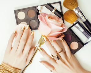 woman hands with golden manicure and many rings holding brushes, makeup artist stuff stylish, pure close up pink