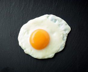 fried egg on black background