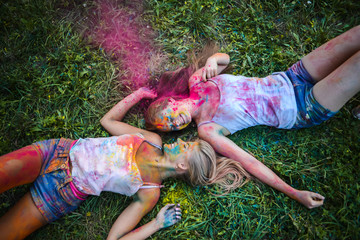 girls celebrate Indian holi festival with colorful paint powder on faces and body