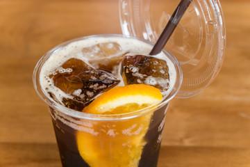 Glass of iced orange tonic lemon tea with slice of orange on wooden table