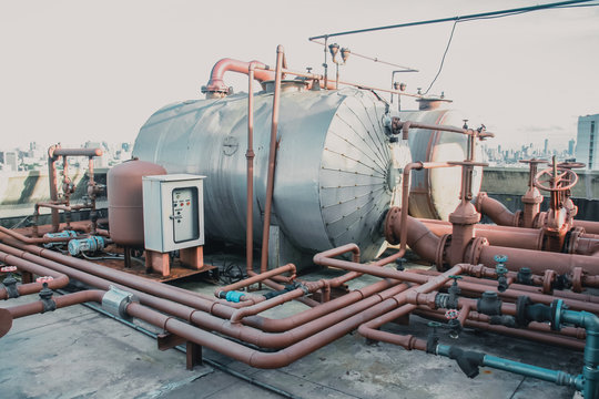 industrial boiler tank and large pipe top of hospital building.