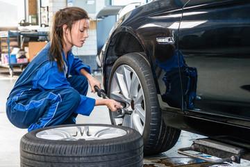 Female Mechanic Changing Car Tire At Automobile Shop